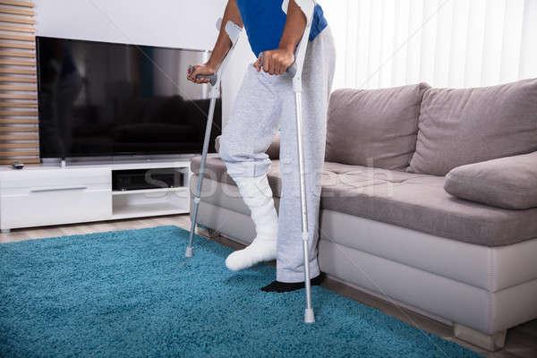 Hombre fractura en la pierna caminando alfombra muletas azul Foto stock © AndreyPopov