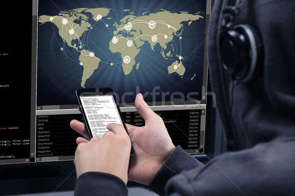 Hacker Using Mobile Phone For Stealing Data From Computer Stock photo © AndreyPopov
