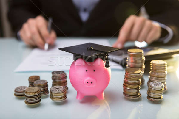 Close-up Of Piggy Bank Wearing Graduation Hat And Stacked Coins Stock photo © AndreyPopov