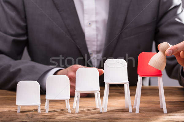 Businessperson Placing Pawn On Red Chair Stock photo © AndreyPopov