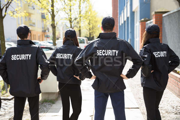 Rear View Of Security Guards Standing In A Row Stock photo © AndreyPopov
