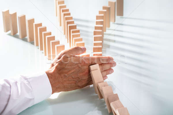 Businessman Stopping Wooden Blocks From Falling On Desk Stock photo © AndreyPopov