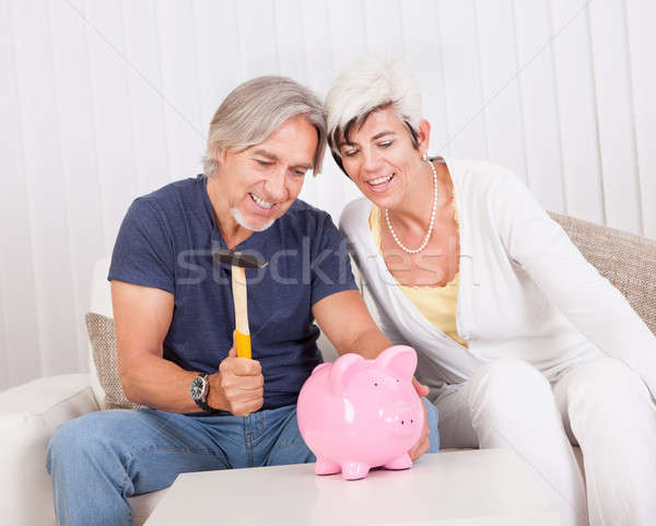 Senior couple raiding a piggybank Stock photo © AndreyPopov
