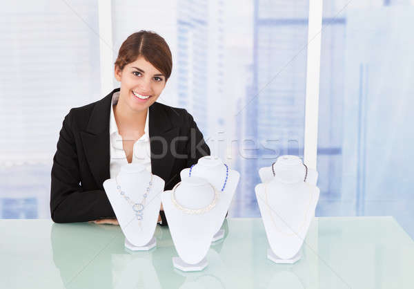 Confident Saleswoman Displaying Jewelry At Desk Stock photo © AndreyPopov