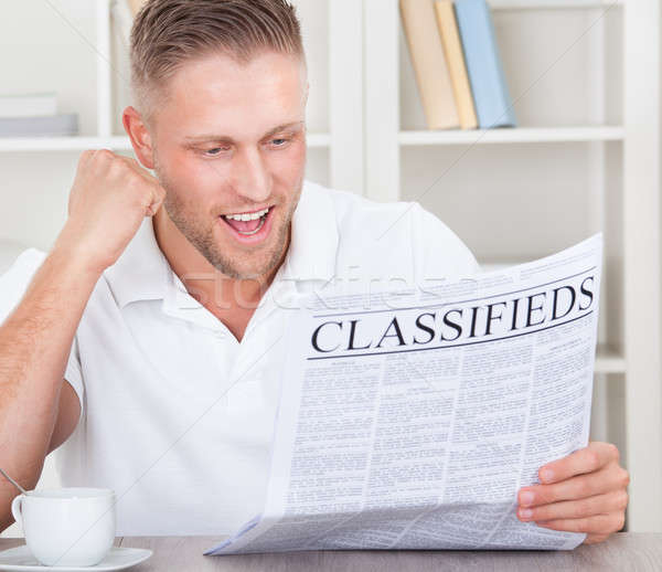 Excited man reading the classifieds cheering Stock photo © AndreyPopov