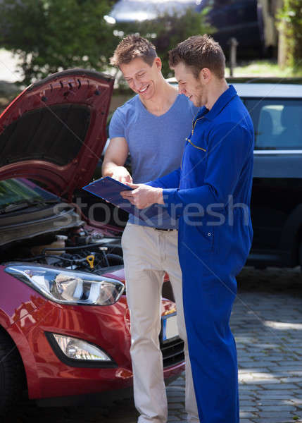 Mechanic Showing Clipboard To Customer By Breakdown Car Stock photo © AndreyPopov