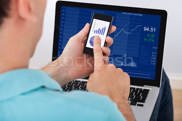 Man Analyzing Stock Market Using Smartphone And Laptop Stock photo © AndreyPopov