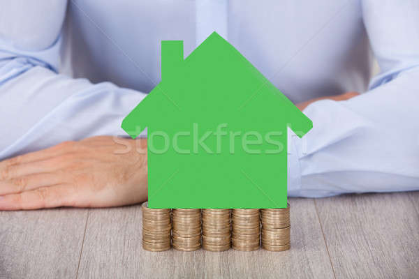 Businessman With Green House Model On Stacked Coins Stock photo © AndreyPopov