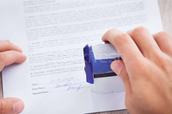 Businessman Stamping Contract Paper On Table Stock photo © AndreyPopov