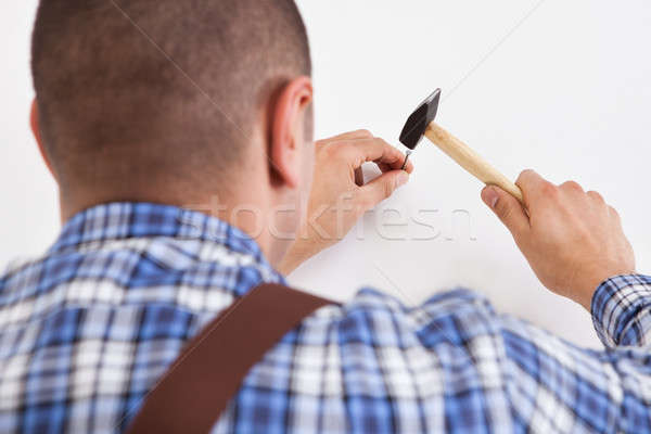 Hands Hammering Wall With Nail Stock photo © AndreyPopov