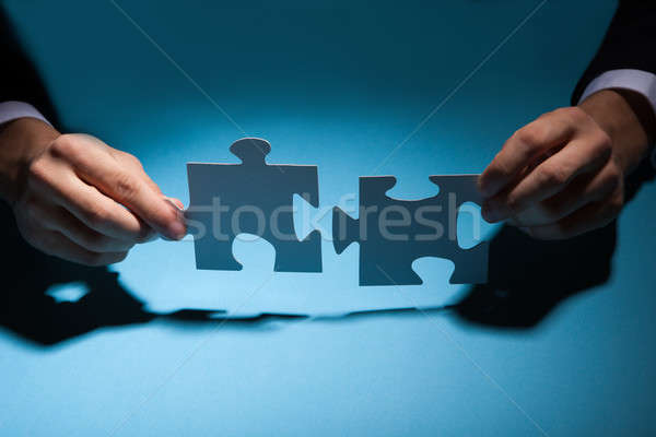 Businessman Joining Puzzle Pieces At Desk Stock photo © AndreyPopov