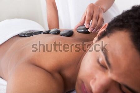 Hand Placing Lastone On Man's Back In Spa Stock photo © AndreyPopov