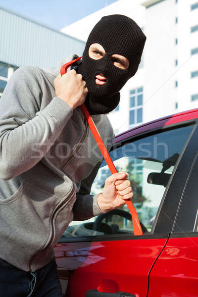 Stock photo: Thief In Hooded Jacket And Balaclava Opening Car's Door