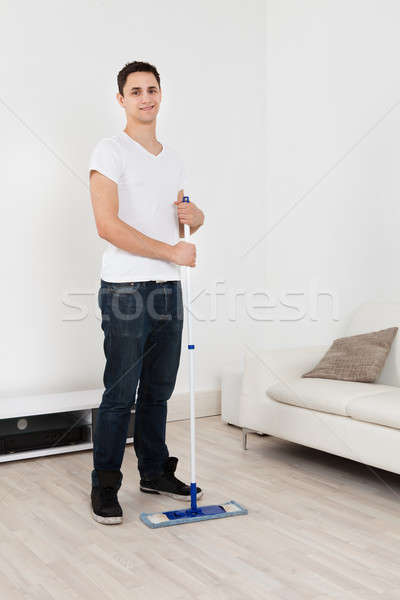 Young Man Mopping Floor At Home Stock photo © AndreyPopov