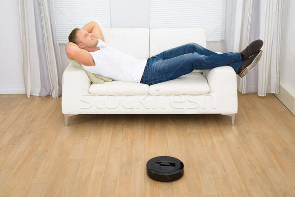 Robotic Vacuum Cleaner In Front Of Man Relaxing Stock photo © AndreyPopov