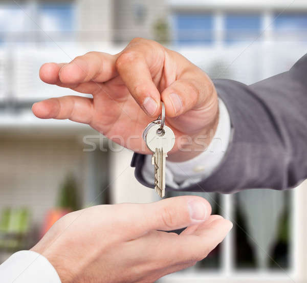Property Agent Giving Keys To Owner Against New House Stock photo © AndreyPopov