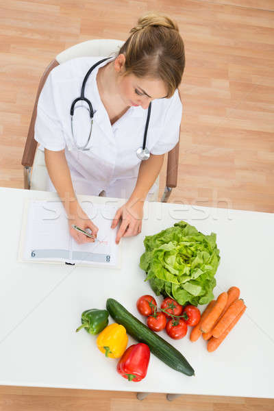 Female Dietician Writing In Diary Stock photo © AndreyPopov