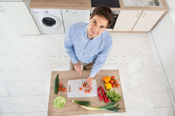 Man Chopping Vegetables In Kitchen Stock photo © AndreyPopov