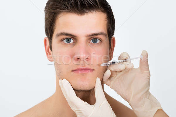 Person Hands Injecting Syringe On Man Face Stock photo © AndreyPopov