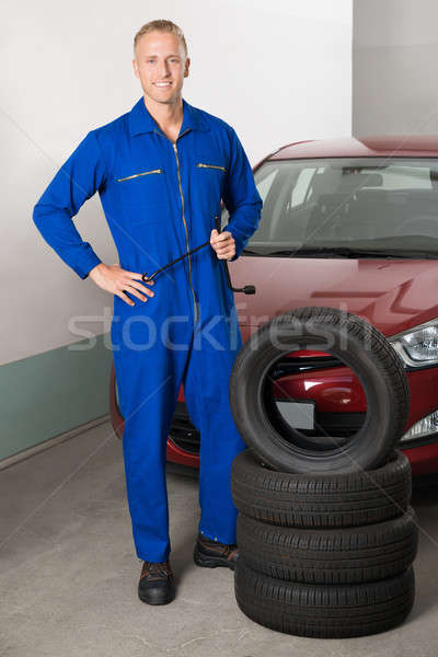 Mechanic Standing Besides Stack Of Tires Stock photo © AndreyPopov