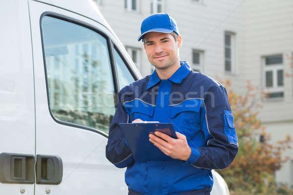 Futár egyenruha tart vágólap teherautó portré Stock fotó © AndreyPopov