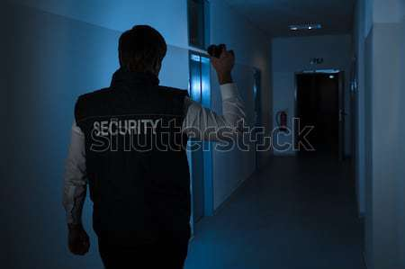 Thief With Flashlight Trying To Break Door Stock photo © AndreyPopov