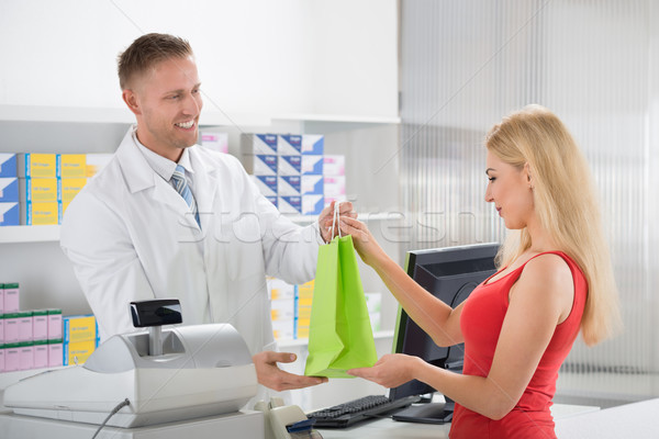 Smiling Pharmacist Giving Medicines To Customer Stock photo © AndreyPopov