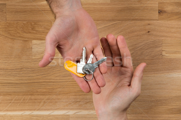 Hand Giving Home Keys To Client At Desk Stock photo © AndreyPopov