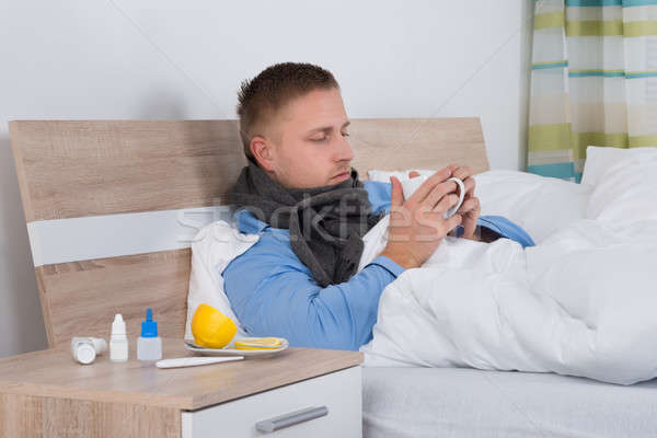 Man Suffering From Cold Lying On Bed Stock photo © AndreyPopov