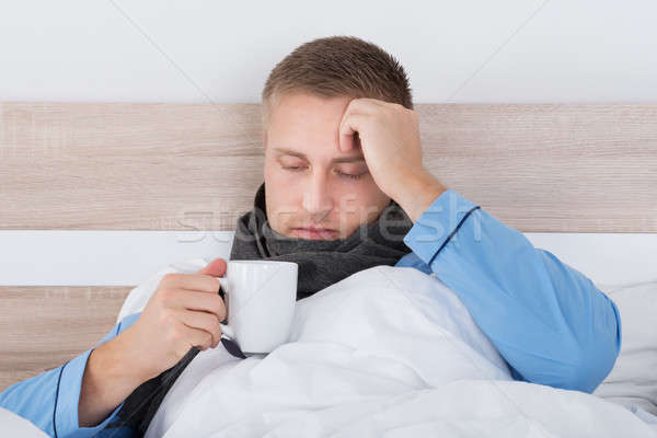 Young Man In Bed With Cup Of Hot Beverage Stock photo © AndreyPopov