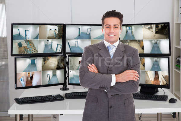 Manager Standing Arms Crossed With Monitors In Background Stock photo © AndreyPopov