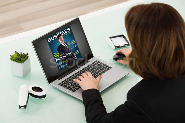 Zakenvrouw lezing online magazine laptop Stockfoto © AndreyPopov
