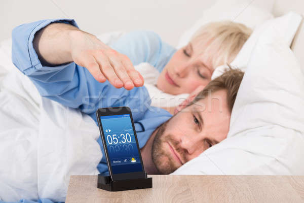 Man On Bed Snoozing Alarm Clock On Cell Phone Stock photo © AndreyPopov