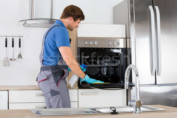 Man In Overall Cleaning Oven Stock photo © AndreyPopov