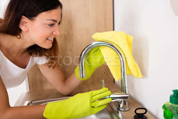Heureux femme nettoyage robinet jeunes acier Photo stock © AndreyPopov