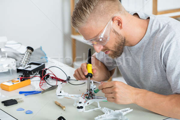 Man In Protective Glasses Assembling Quadrocopter Drone Stock photo © AndreyPopov