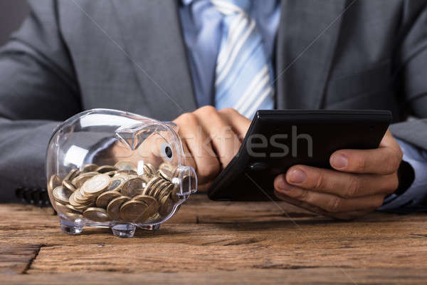 Stock photo: Businessman Using Calculator By Glass Piggybank At Table