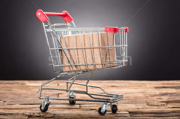 Package In Shopping Cart On Wooden Table Stock photo © AndreyPopov