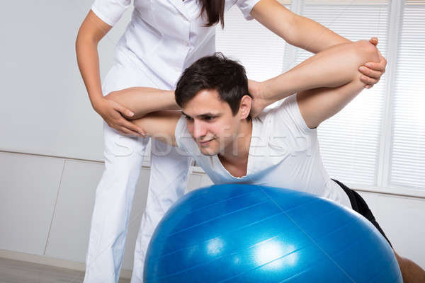 Physiotherapist Assisting Man While Doing Exercise Stock photo © AndreyPopov