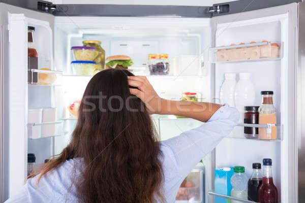 Mylić kobieta patrząc otwarte lodówce widok z tyłu Zdjęcia stock © AndreyPopov