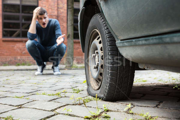 Crouched Man Pointing At Punctured Car Tire Stock photo © AndreyPopov