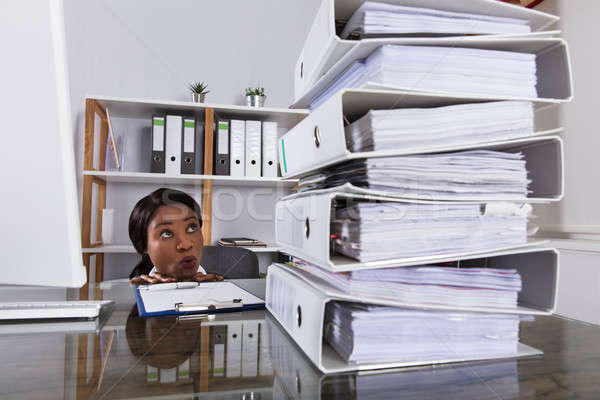 Woman Looking At Stack Of Folders On Desk Stock photo © AndreyPopov