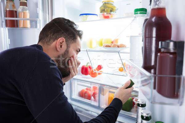 Hombre olor alimentos refrigerador primer plano joven Foto stock © AndreyPopov