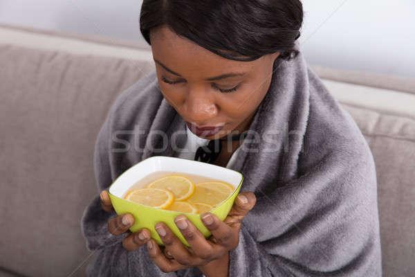 Sick Woman Holding Bowl With Sliced Lemon Stock photo © AndreyPopov