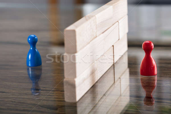 Red And Blue Figurine Paw Separated By Wooden Blocks Stock photo © AndreyPopov