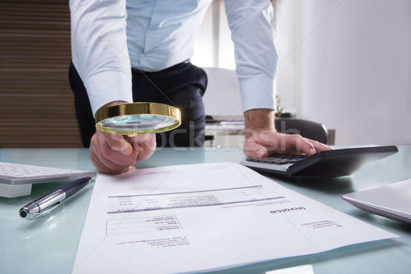 Human Hand Holding Magnifying Glass Over Invoice Stock photo © AndreyPopov