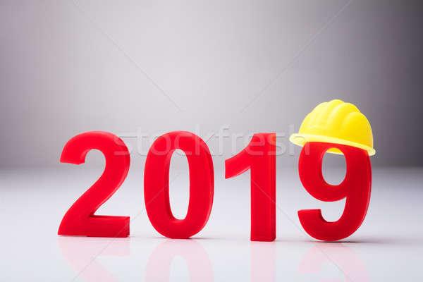 Año amarillo casco de seguridad blanco construcción fondo Foto stock © AndreyPopov