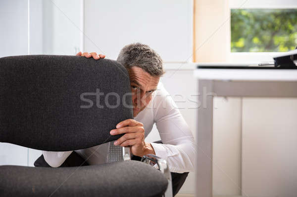 Przestraszony biznesmen za krzesło dojrzały biuro Zdjęcia stock © AndreyPopov