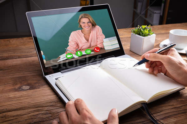 Person Writing On Notebook While Video Chatting Stock photo © AndreyPopov