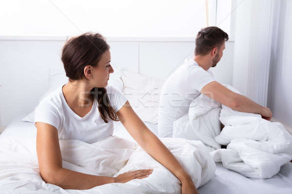 Unhappy Couple Sitting On Bed Stock photo © AndreyPopov